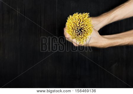 Spaghetti in hands. Top view bunch of  raw spaghetti in male hands on black wood vintage table