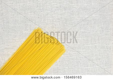 Raw spaghetti flat lay. Bunch of uncooked spaghetti top view on light white canvas