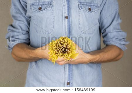 Raw spaghetti in male hands. Handful of uncooked spaghetti. Closeup of man in blue jeans shirt holds bunch of italian pasta