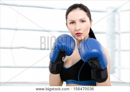 Portrait of a beautiful young woman in boxing gloves on the background of boxing ring