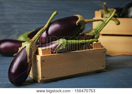 Fresh aubergines in crate on wooden background