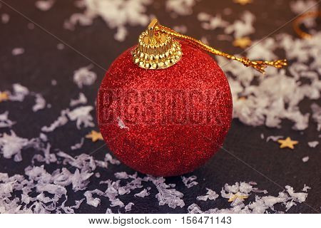 One red satin Christmas ball on black background