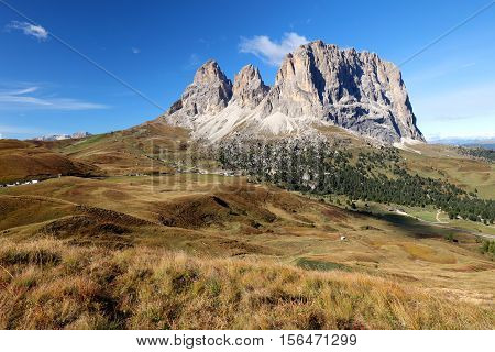 Sassolungo Val Gardena Dolomites Italy. The Sassolungo alp standing over colorful fields during the summer season in Val Gardena Trentino Alto Adige Italy.