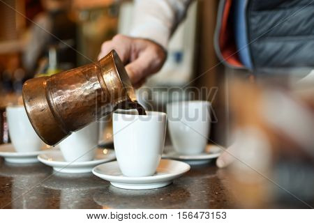 Man pouring turkish / greek coffee from a pot in a white porcelain cup