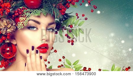 Christmas Woman Makeup. Winter Fashion Girl. Beautiful New Year and Christmas Tree Holiday Hairstyle, Make up, manicure. Beauty Model on winter Background. Creative Hair style decorated with Baubles