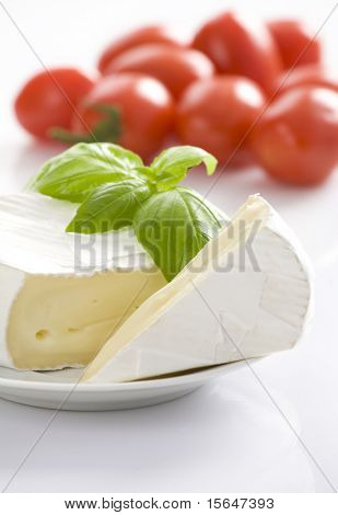 Mouldy cheese with basil leaves on white plate. Some tomatoes in background. All on white background