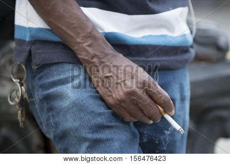 Man with cigarette in hand coming out smoke