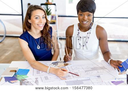 Young women sitting at a desk in an office and working on blueprint
