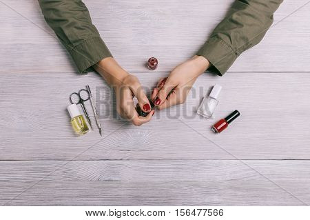 Female Hands Make Manicure And Paint Nails With Red Lacquer
