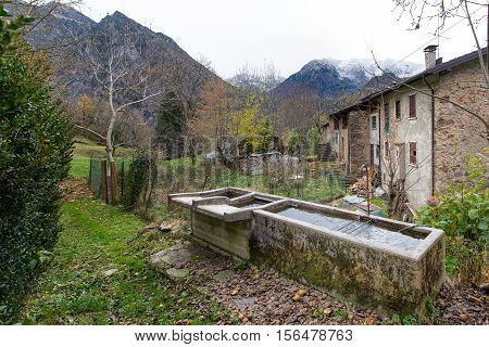 Old fountains in a village of the Italian alps in autumn