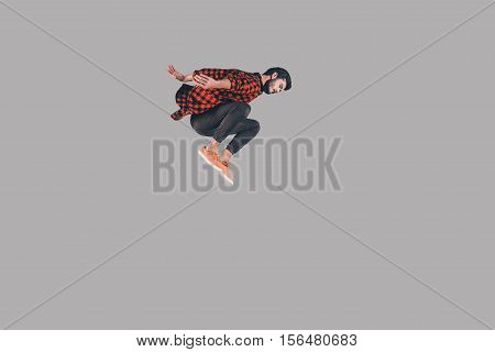 In motion. Mid-air shot of handsome young man jumping and gesturing against background