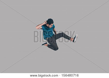 Cool and free. Mid-air shot of handsome young man in cap jumping and gesturing against background