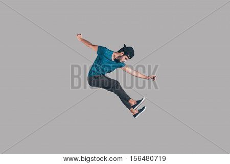 Freedom in every move. Mid-air shot of handsome young man in cap jumping and gesturing against background