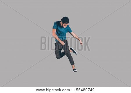 Young and cool. Mid-air shot of handsome young man in cap jumping and gesturing against background