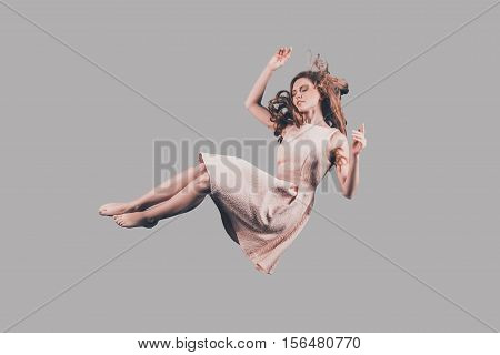 Woman in mid-air. Studio shot of attractive young woman hovering in air