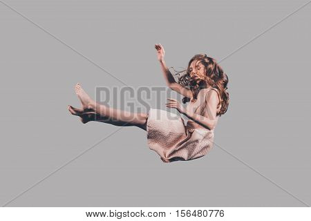 Falling to nowhere. Studio shot of attractive young woman hovering in air