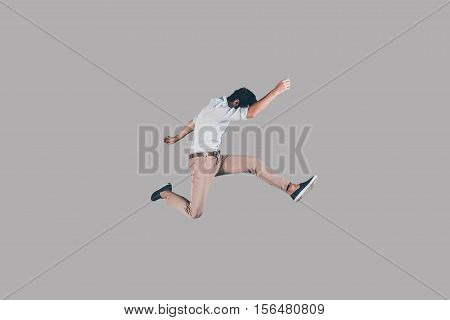 Keep moving! Mid-air shot of handsome young man jumping and gesturing against background