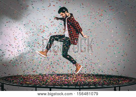 Trampoline fun. Mid-air shot of handsome young man jumping on trampoline with confetti all around him