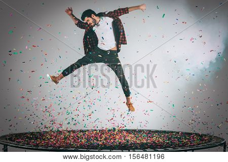 Unleashed fun. Mid-air shot of handsome young man jumping on trampoline with confetti all around him