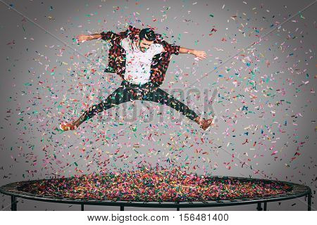 Fun in motion. Mid-air shot of handsome young man jumping on trampoline with confetti all around him