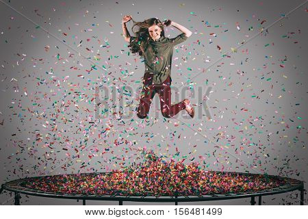 Colorful fun. Mid-air shot of beautiful young woman jumping on trampoline with confetti all around her