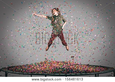 Fun in motion. Mid-air shot of beautiful young woman jumping on trampoline with confetti all around her