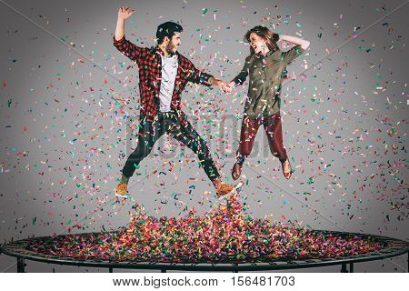 Trampoline fun. Mid-air shot of beautiful young cheerful couple holding hands while jumping on trampoline together with confetti all around them