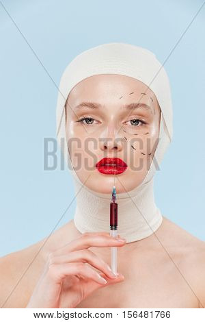 Model with syringe. unusual image. isolated biege background