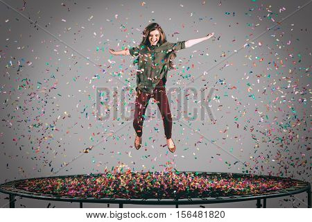 Beauty on trampoline. Mid-air shot of beautiful young woman jumping on trampoline with confetti all around her