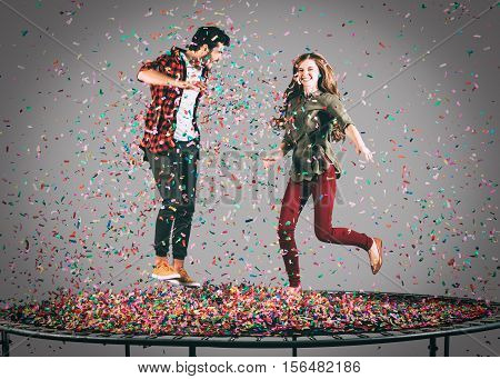Colorful fun. Mid-air shot of beautiful young cheerful couple jumping on trampoline together with confetti all around them