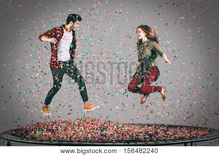 Mid-air fun. Mid-air shot of beautiful young cheerful couple jumping on trampoline together with confetti all around them