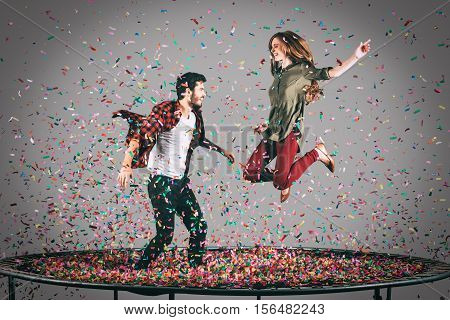 Just for fun. Mid-air shot of beautiful young cheerful couple jumping on trampoline together with confetti all around them