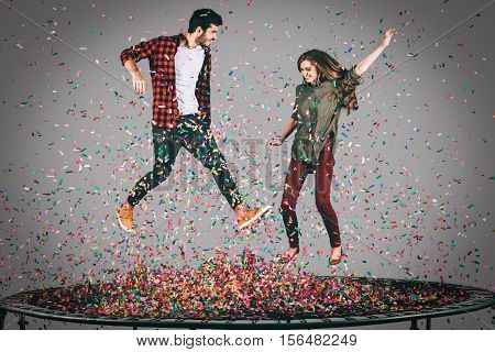 Confetti fun. Mid-air shot of beautiful young cheerful couple jumping on trampoline together with confetti all around them