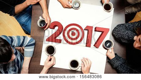 People sitting around table drinking coffee against composite image of numbers with bulls eye arrow