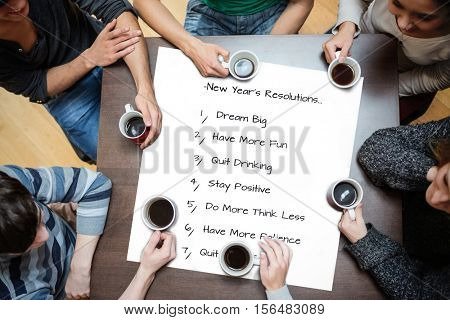People sitting around table drinking coffee against new years resolutions