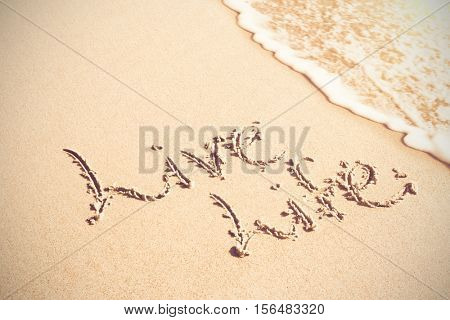 Live life written text on sand at beach