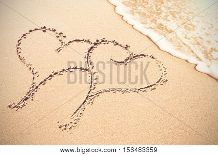 Two heart shapes inscribe on sand at beach
