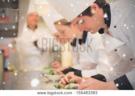 Snow falling against culinary class in kitchen making salads
