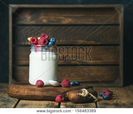 Glass jar of white yogurt with fresh berries and peach on serving board over rustic table, wooden tray as background, copy space, selective focus, horizontal composition