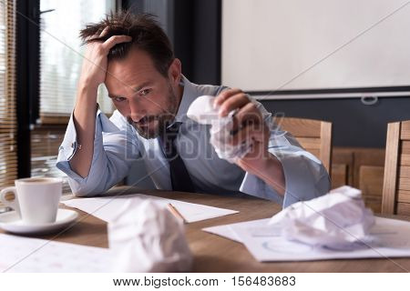 Need new ideas. Exhausted cheerless depressed man holding his head and crumpling a sheet of paper while dealing with a problem