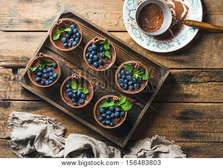 Homemade Tiramisu dessert in glasses with cinnamon, mint and fresh blueberries in wooden tray and sieve with cocoa powder in white plate over rustic wooden background, top view, copy space