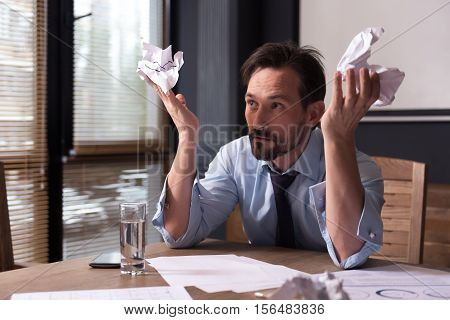 Do not know what to do. Sad miserable depressed man holding crumpled paper and throwing it up while working long hours on a project
