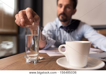 Taking sedatives. Selective focus of a small white sedative pill being put in the water by a cheerless exhausted depressed man while coping with stress