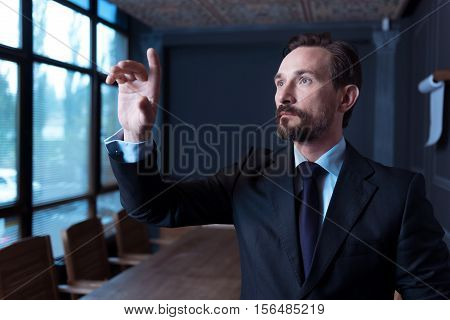 Age of technology. Good looking confident bearded man standing in the conference hall and touching the virtual sensory panel while working on it