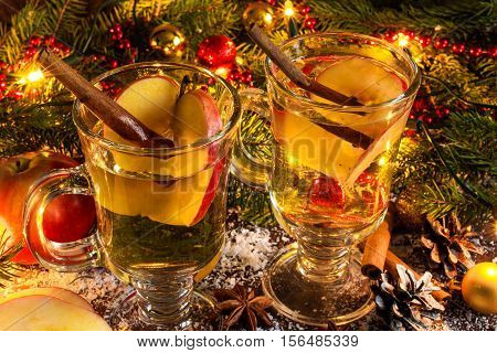 Mulled cider with cinnamon apple anise and citrus with christmas lights and decorations. close up