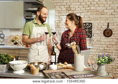 Loving couple drinking red wine, clinking glasses in kitchen, cooking together.