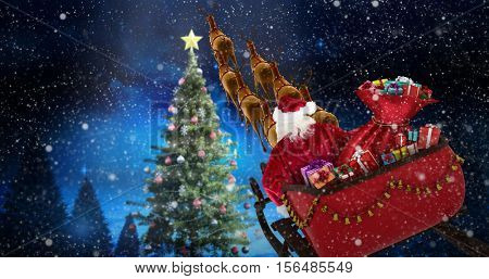 High angle view of Santa Claus riding on sled during Christmas against forest at night with christmas tree