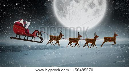 Side view of Santa Claus riding on sleigh during Christmas against balcony overlooking coastline at night