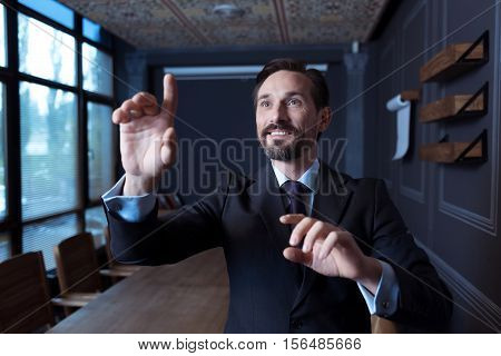 Involved in the activity. Happy positive confident man standing in front of a virtual sensory panel and pressing his hand to the screen while working in the virtual reality