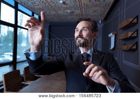 Technological progress. Handsome nice bearded man standing in the conference room and working on the imaginary sensory screen while being in the virtual reality